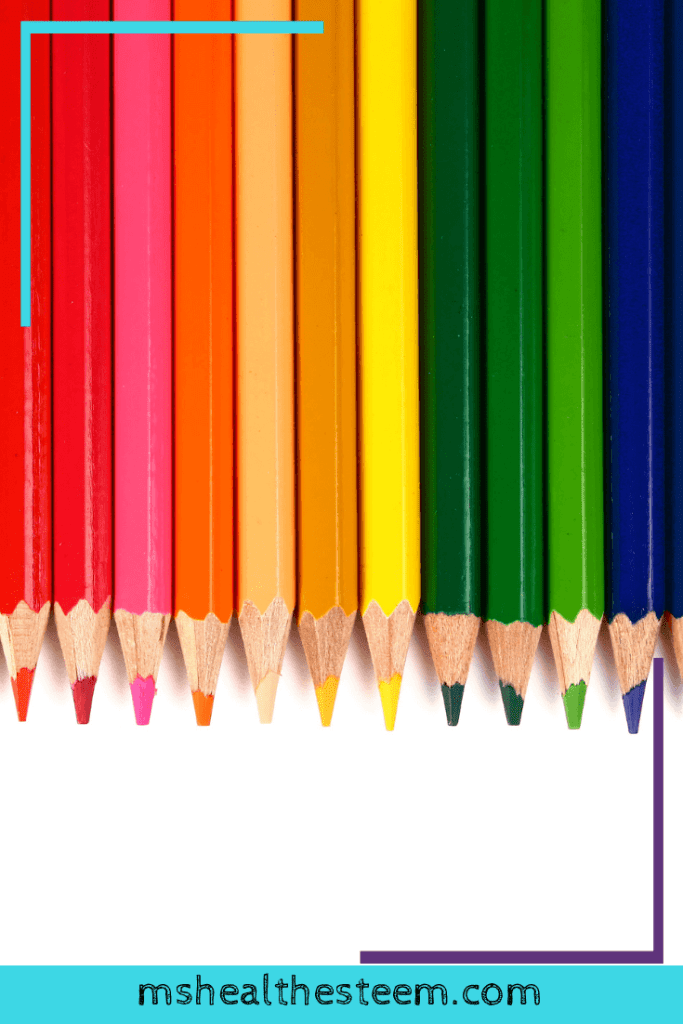 A line of pencil crayons sit at the top of a white backdrop, arranged horizontally.
