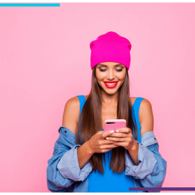A woman stands in from of a pink backdrop, wearing a pink tuque. She looks down at the phone she's holding and smiles.