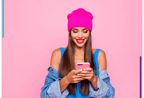 A woman stands in from of a pink backdrop, wearing a pink tuque. She looks down at the phone she