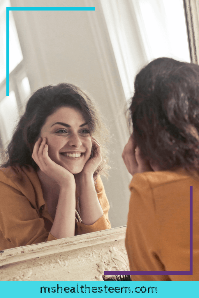 A woman rests her head on her hands and looks at herself in the mirror as she smiles