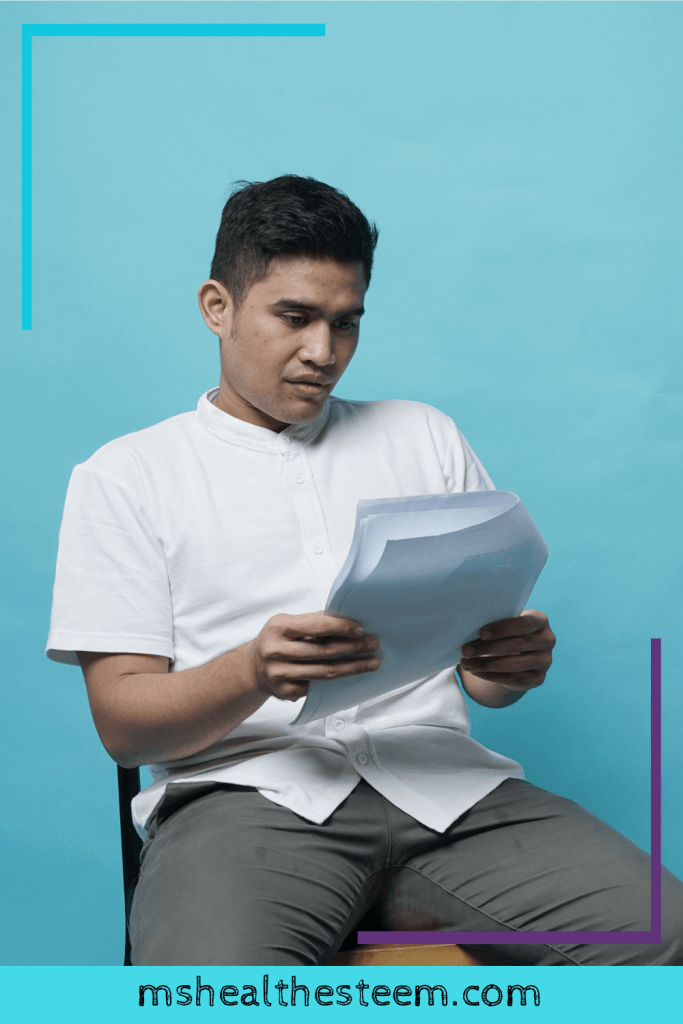 A man sits and looks at a document full of practice interview questions. The background is light blue.