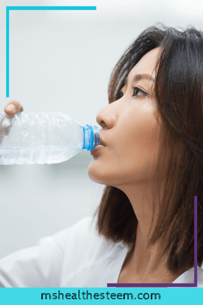 Side view of a woman drinking more water from plastic bottle