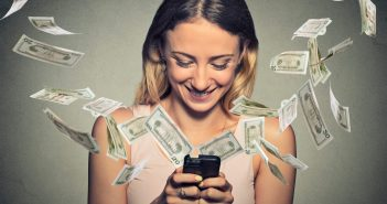 Happy woman using smartphone with dollar bills flying away from screen