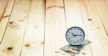Clock and  money on wooden background, vintage color effect