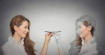 Woman drawing a picture, sketch of herself grey wall background