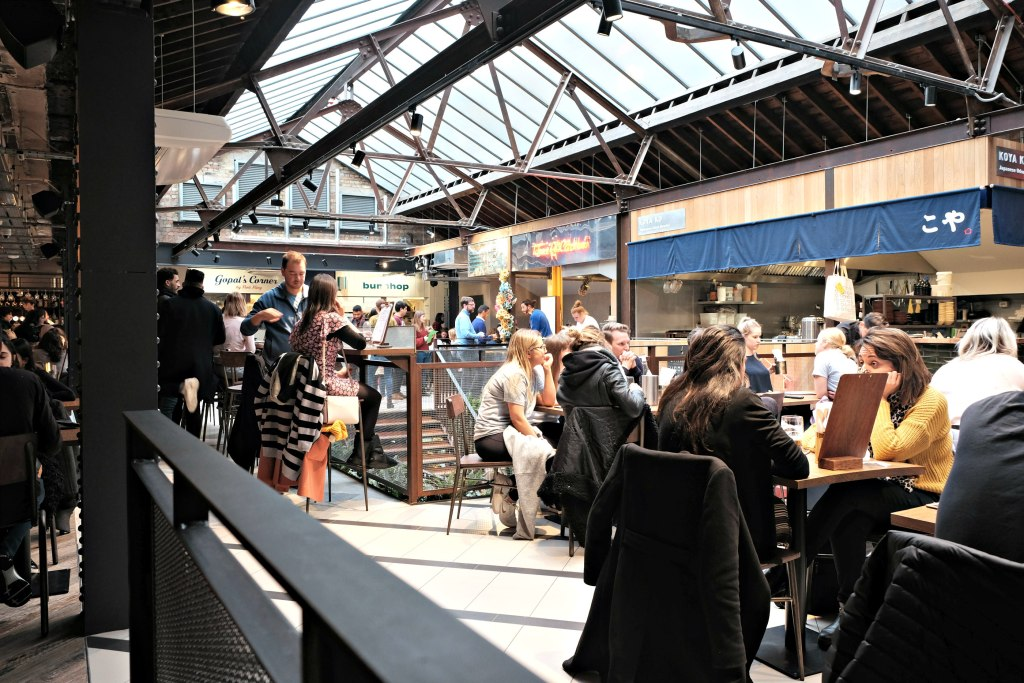 Picture of the inside of the Victoria Market Halls with glass roof and lots of people eating and drinking.