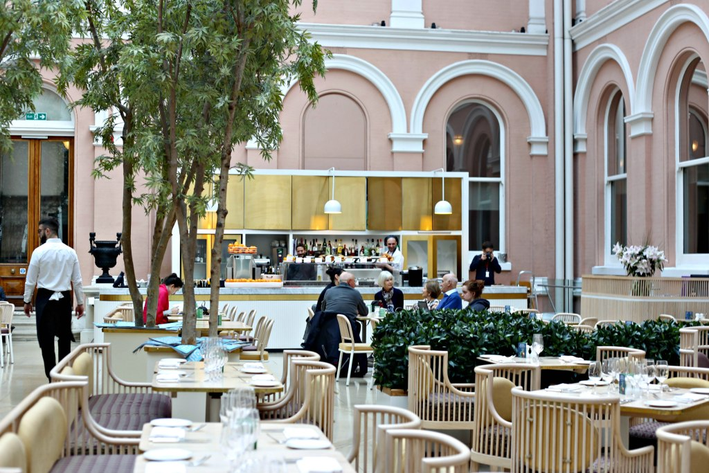 Picture of resturant at the Wallace Museam with the gold bar area and people having coffee.