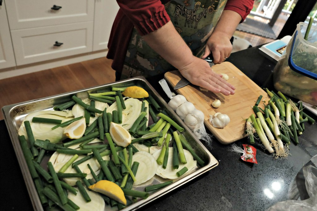 Picture is of my mums hands squashing garlic.  There is a oven pan full of fennal, lemons and spring onion showing the mid process of cooking.