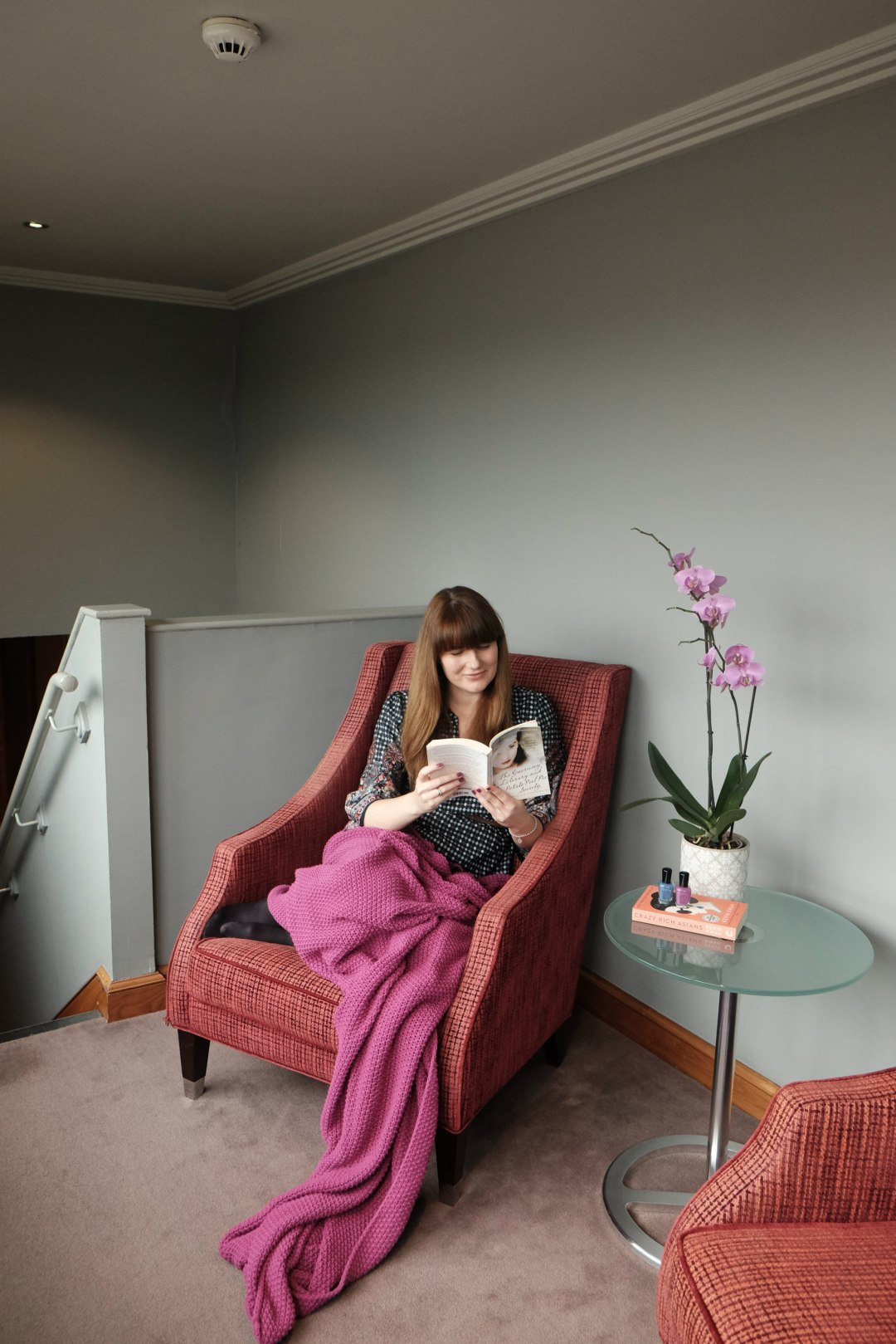 Another image of me on the armchair with the blanket draped over me!  There is a stack of books for my spring reading list.
