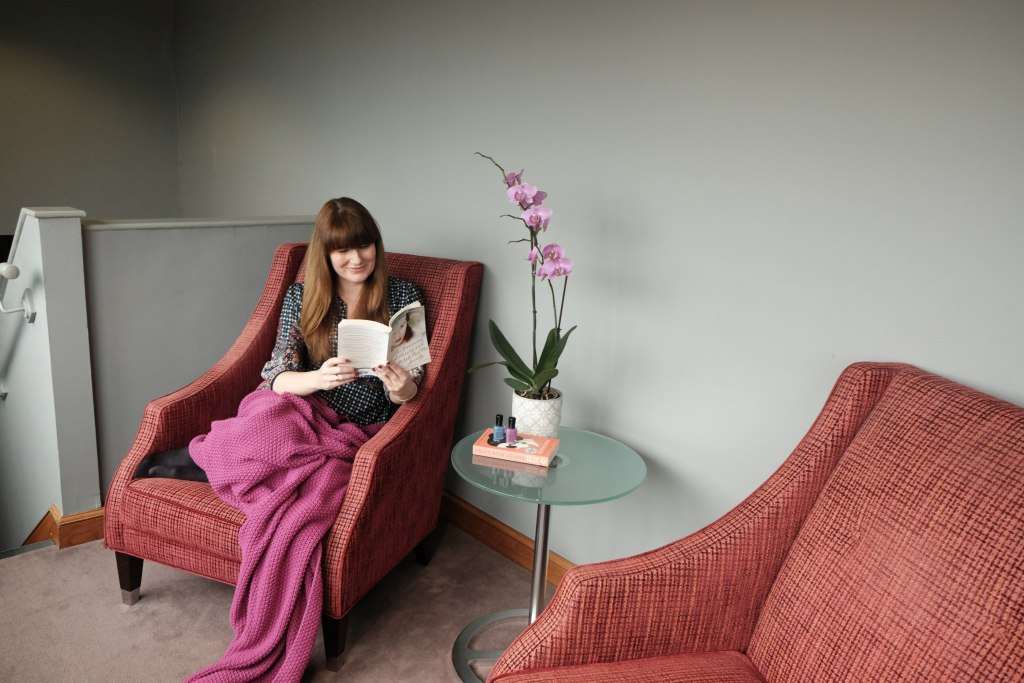 This picture is of me reading on a read armchair with ah purple blanket over me.  There is a stack of books for my spring reading list.