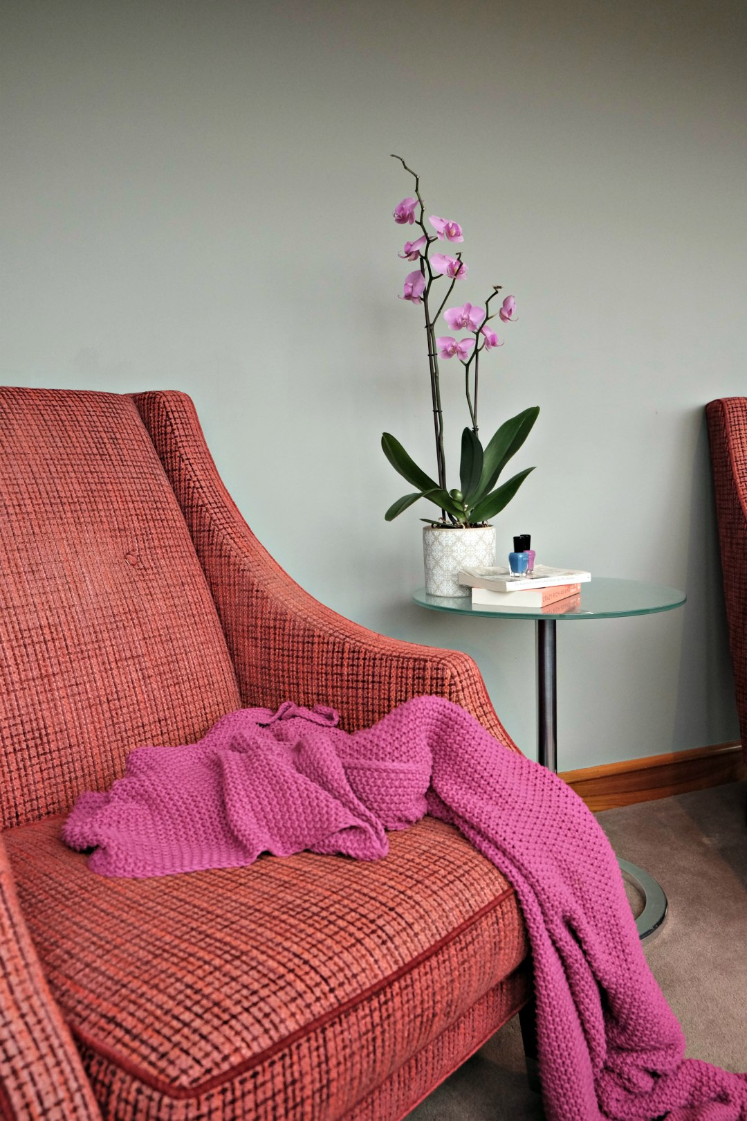 This image is of the red armchair with the purple blanket draped over it.  I nthe background are books on a side table.  There is a stack of books for my spring reading list.