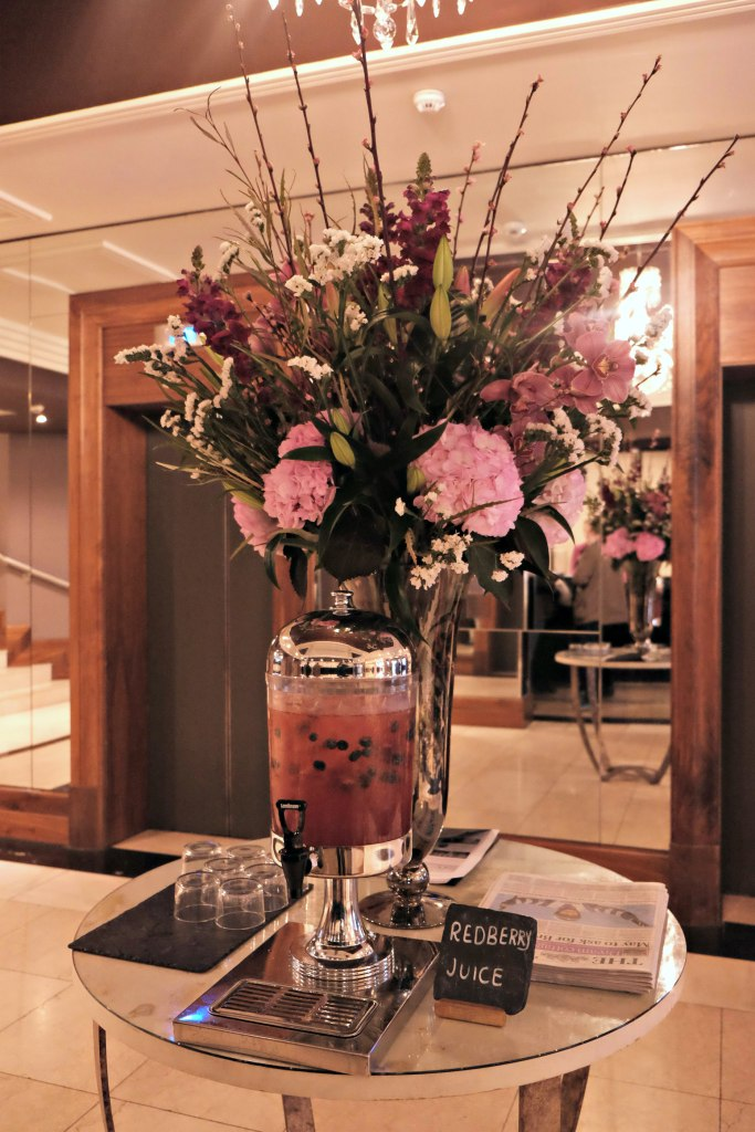 Picture of the main lobby with a huge bouquet of flowers and red berry drink bowl with glasses for guest to try.