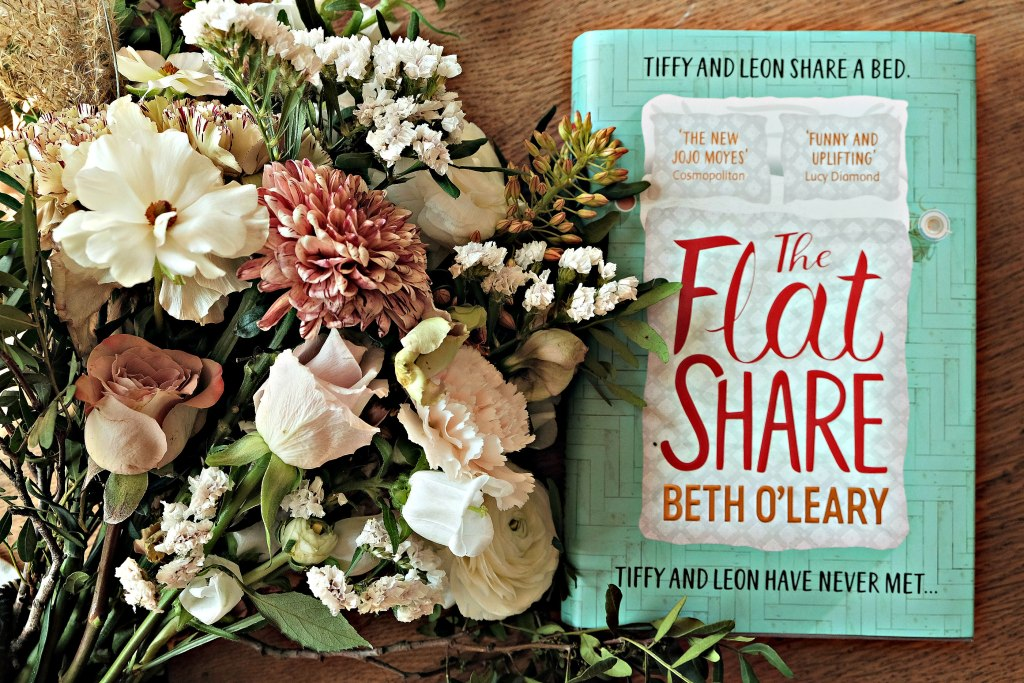 A picture of bouquet of flowers next to The Flat Share book by Beth O'Leary.  This article is a book review.