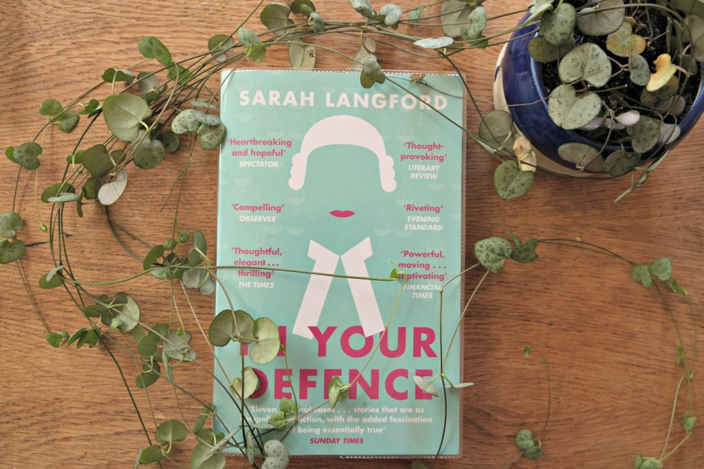 Picture is taken of the front over of the book with a string of plants heart next to it.  In Your Defence by Sarah Langford Book Review.
