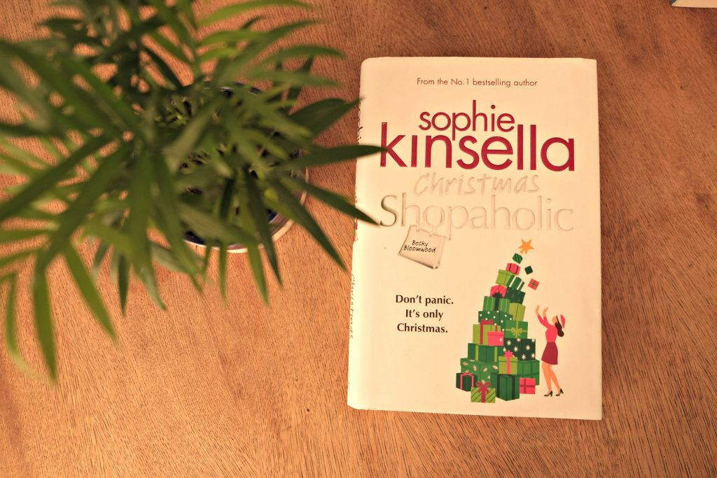Christmas Shopaholic by Sophie Kinsella.  Picture of the book and a plant on my table.