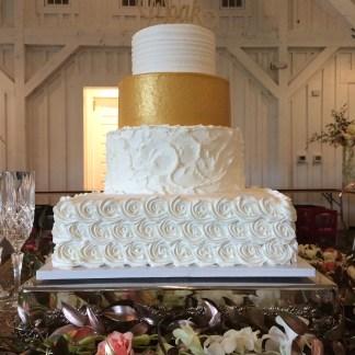 gold wedding cake with rosettes