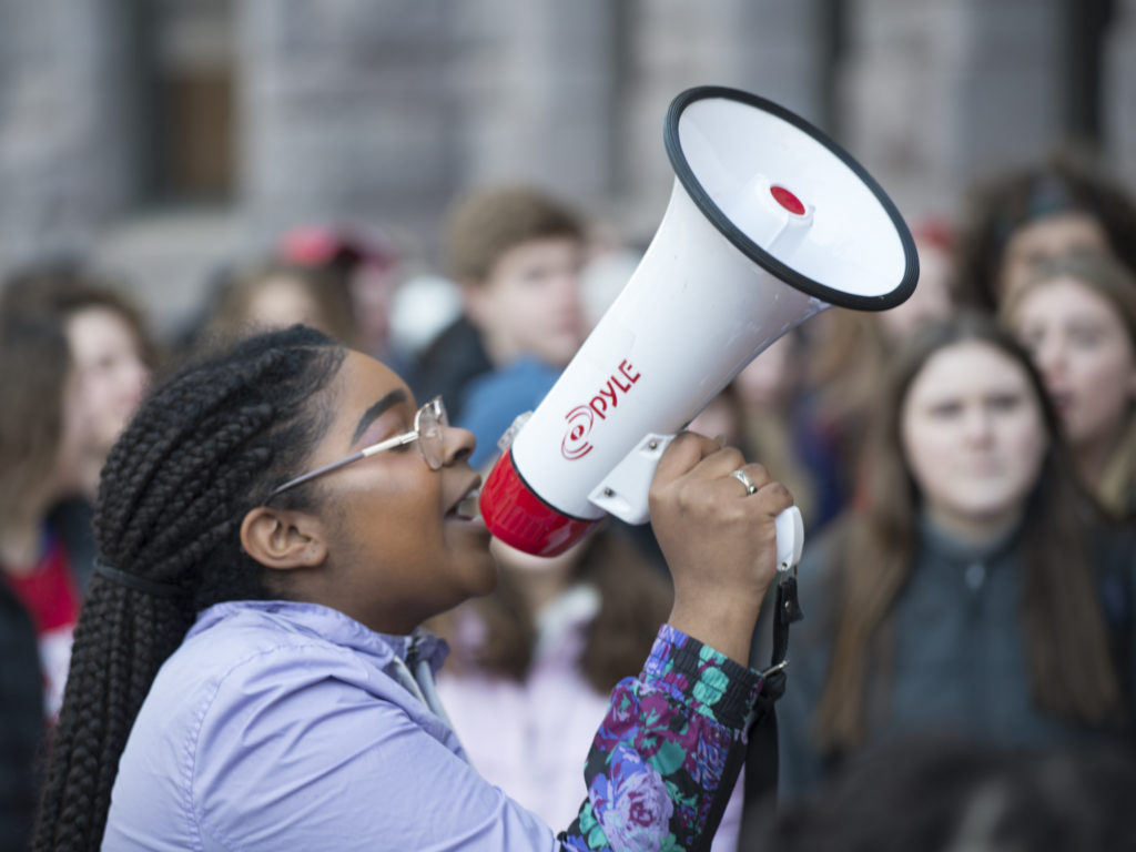 a young girl holds a megaphone at a protest