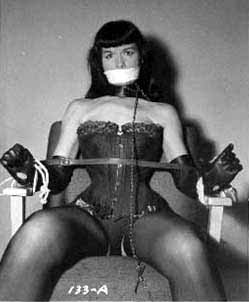 bdsm basics peterborough kink classes kinky workshops youre welcome ptbo [Image Description: Betty page, a white woman with long black hair and bangs sits bound to a chair by rope and a spreader bar. she has tape over her mouth and is dressed in leather lingerie]