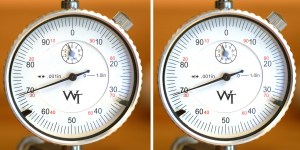 """The """"70"""" on the dial indicator isn't a measurement of anything; it just happened to be the position of the indicator. What matters is the area the indicator sweeps, measuring points about the circumference of the case. More needle movement means more warping. This pair of photos shows the amount of warp on a new case measured using a V-block-style concentricity fixture with a dial indicator. Even new, they're not perfect."""