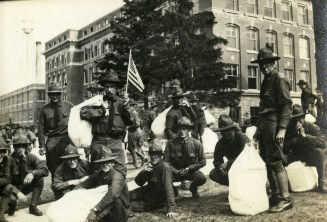 Soldier holding an American flag. The Engineering Building can be seen in the background, circa 1918 (A006441)