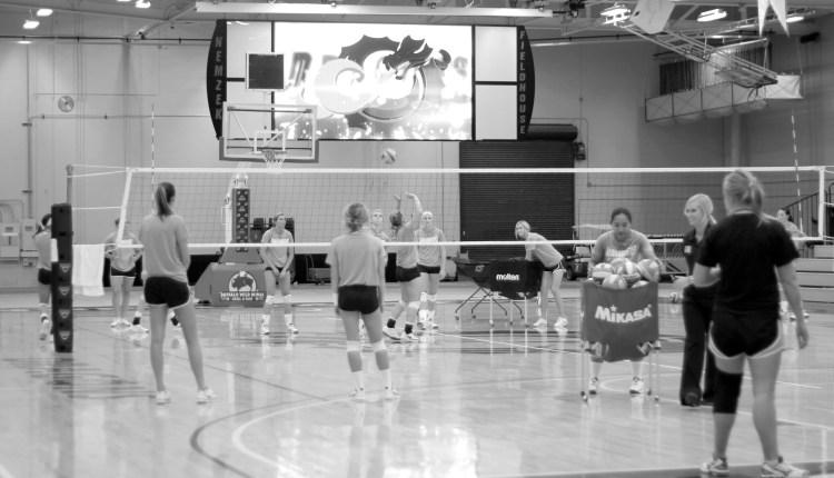 The girls volleyball team practicing under the new jumbotron in Nemzek.
