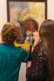 Grand opening reception at the Mount Baker Neighborhood Center for the Arts. Director Barbara Oswald guides a blind guest to feel an oil painting created by a blind artist.
