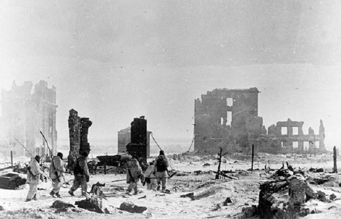 Группа советских саперов со щупами направляется на разминирование в центре разрушенного Сталинграда.