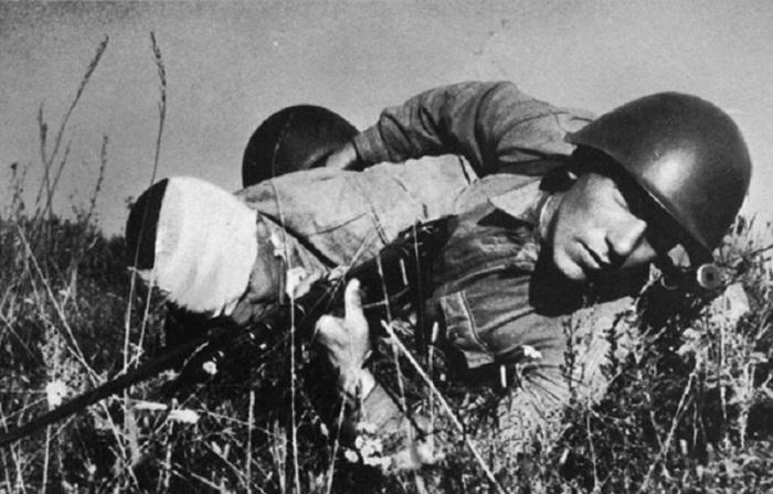 Красноармеец вытаскивает раненого товарища с поля боя на подступах к Сталинграду.