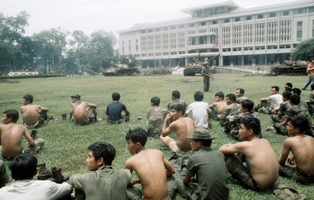 Захваченные южновьетнамские солдаты сидят на широкой лужайке после того, как войска Северного Вьетнама захватили президентский дворец в Сайгоне. 30 августа