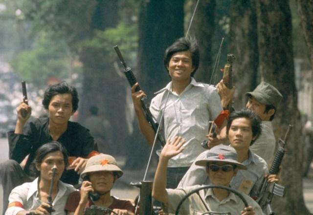 Транспортные средства, переполненные северо-вьетнамскими солдатами, проходят через город, празднующий победу. 30 апреля