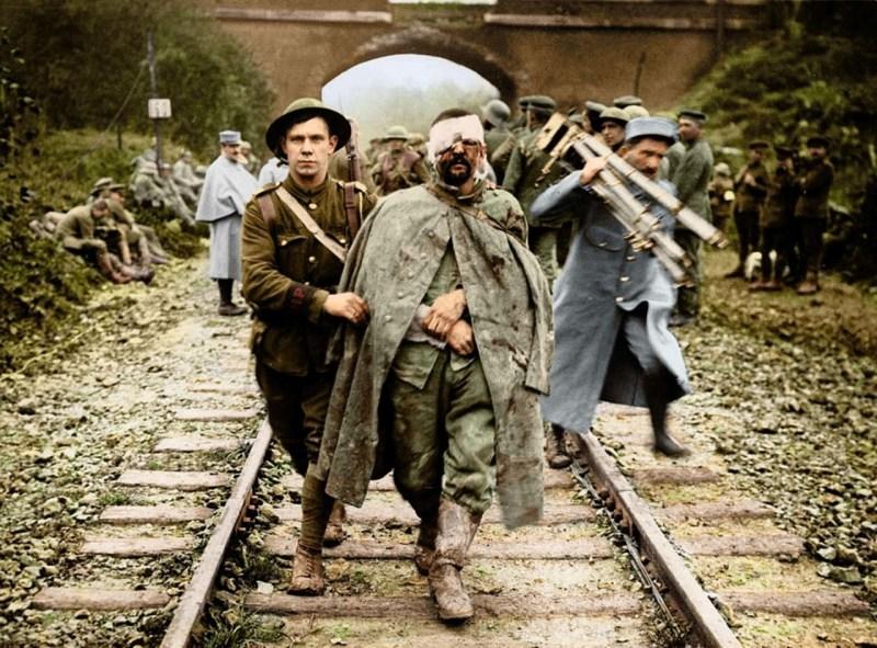 Британский солдат помогает раненому немецкому заключенному, 1916 г. архивное фото, колоризация, колоризация фотографий, колоризированные снимки, первая мировая, первая мировая война, фото войны