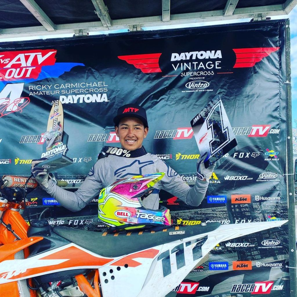 Samuel Posada poses with his 125c class first place trophy and plate at Daytona Amateur Supercross podium.