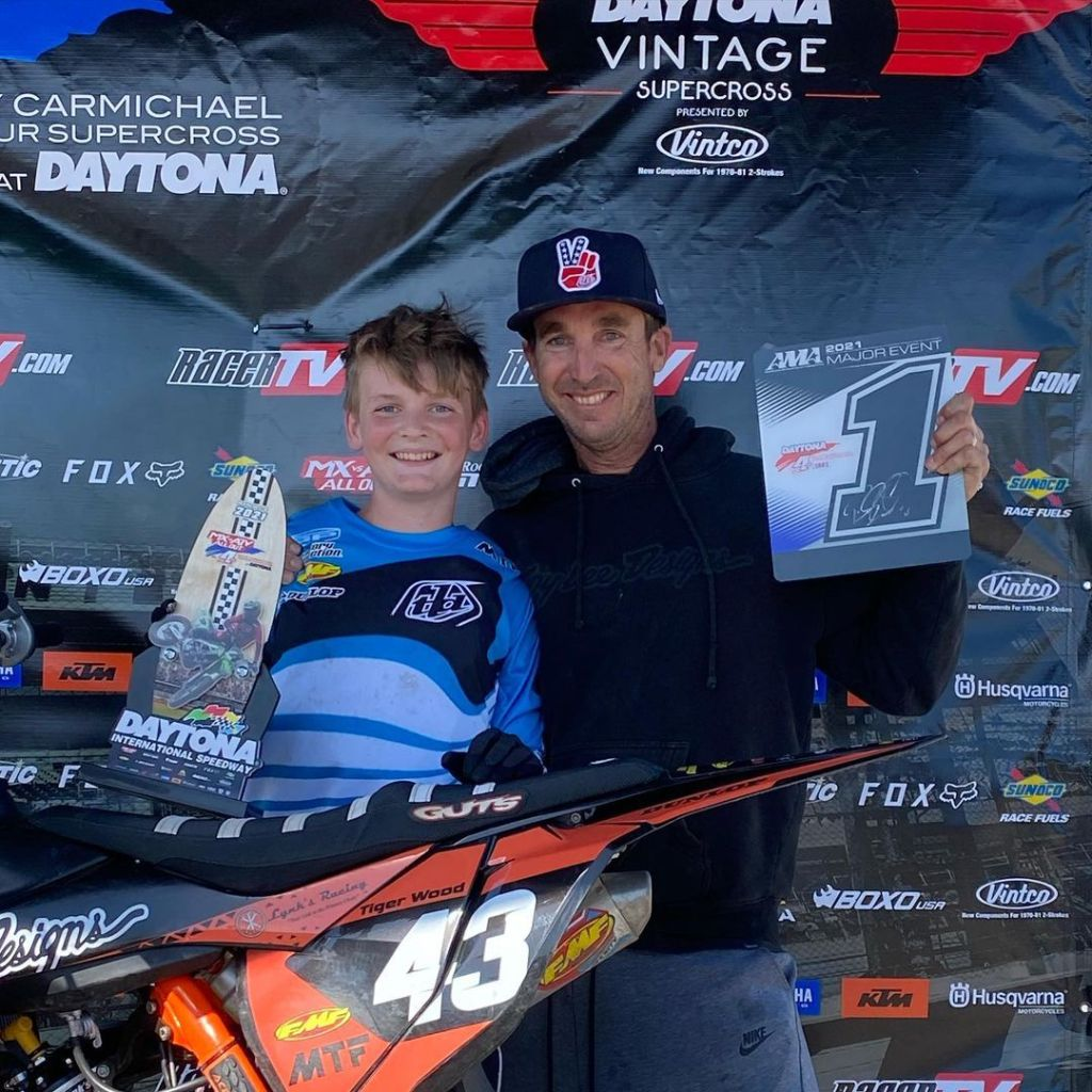 Tommy Wood poses with his dad on the podium, holding his first place trophy and plate at Daytona Amateur Supercross