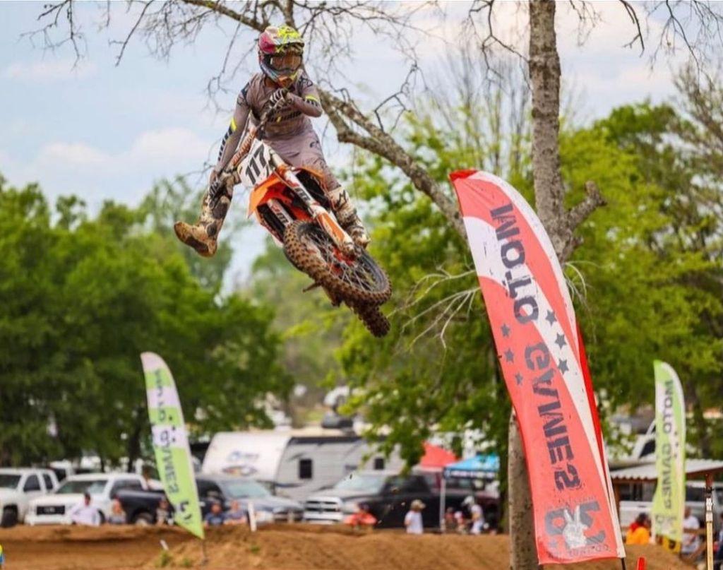 Samuel Posada jumps  through a rhythm section at the motocross race.