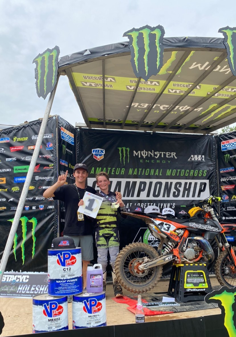 Thomas Wood holds up a number 1 plate on the podium at Loretta's Amateur Nationals.