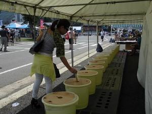 第五陣越前おおのとんちゃん祭のスタッフをしました。 目当ての桶に投票する女性/どこまでもアマチュア