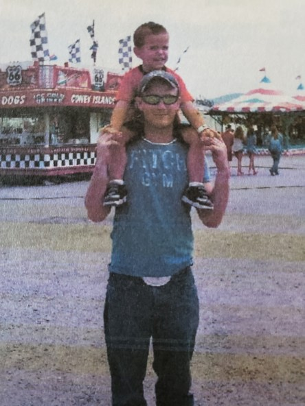 Aaron holds his son Colton on his shoulders at a fair.
