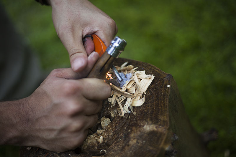 generating sparks with fire starter steel and opinel