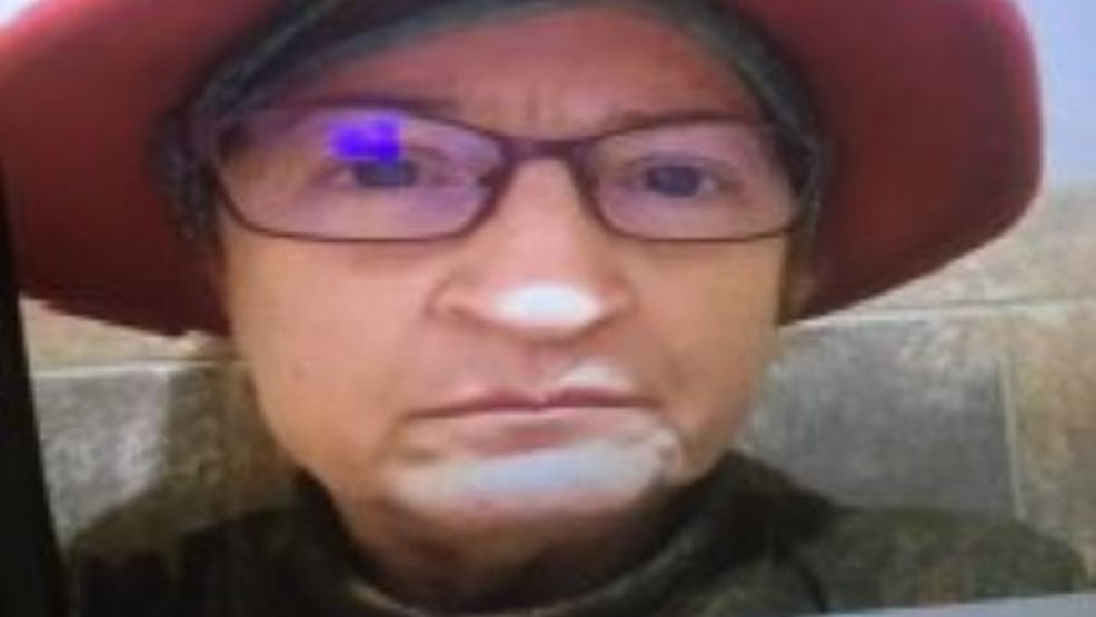 The missing woman looks into the camera, wearing a red hat and glasses.
