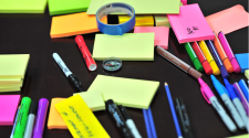 A table covered in post-it notes, pens, markers and tape.