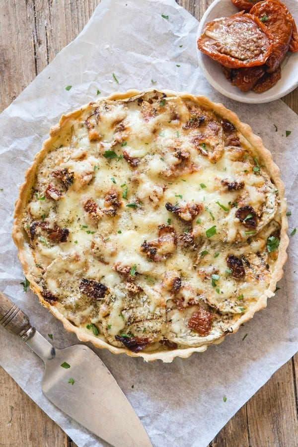 An easy Savory Pie, the perfect way to use up summer eggplant. Layers of eggplant, two types of cheese, spices and dried tomatoes. The perfect combination for an appetizer or main dish.