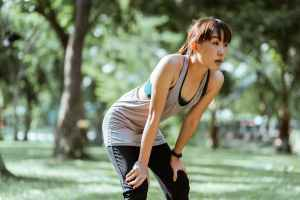 young asian sportswoman having rest after workout in park