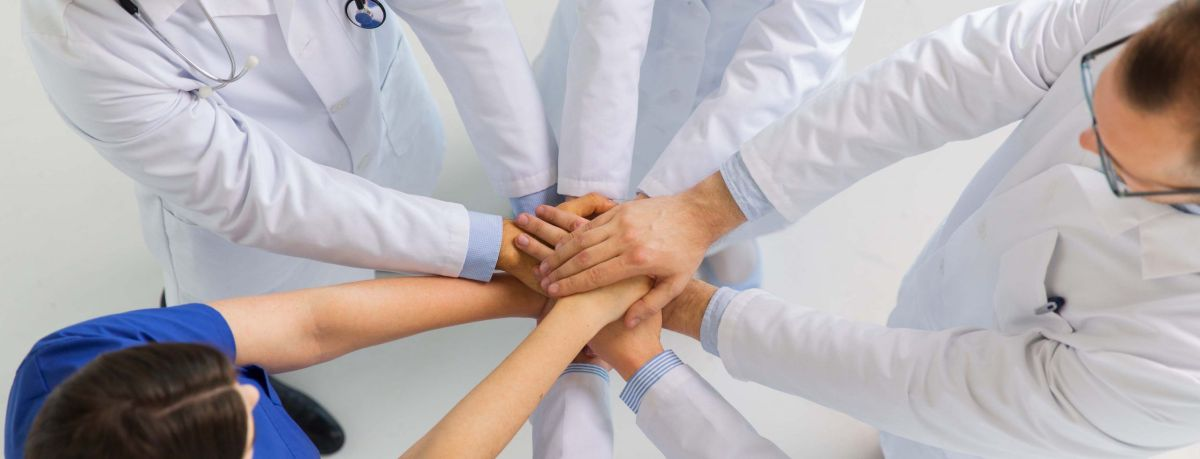 group of doctors with hands together at hospital P2MV63N scaled - NOVEDADES