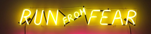 neon sign reading run from fear