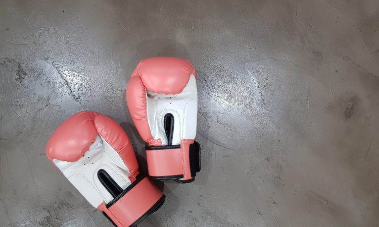 Pink boxing gloves on a gray surface