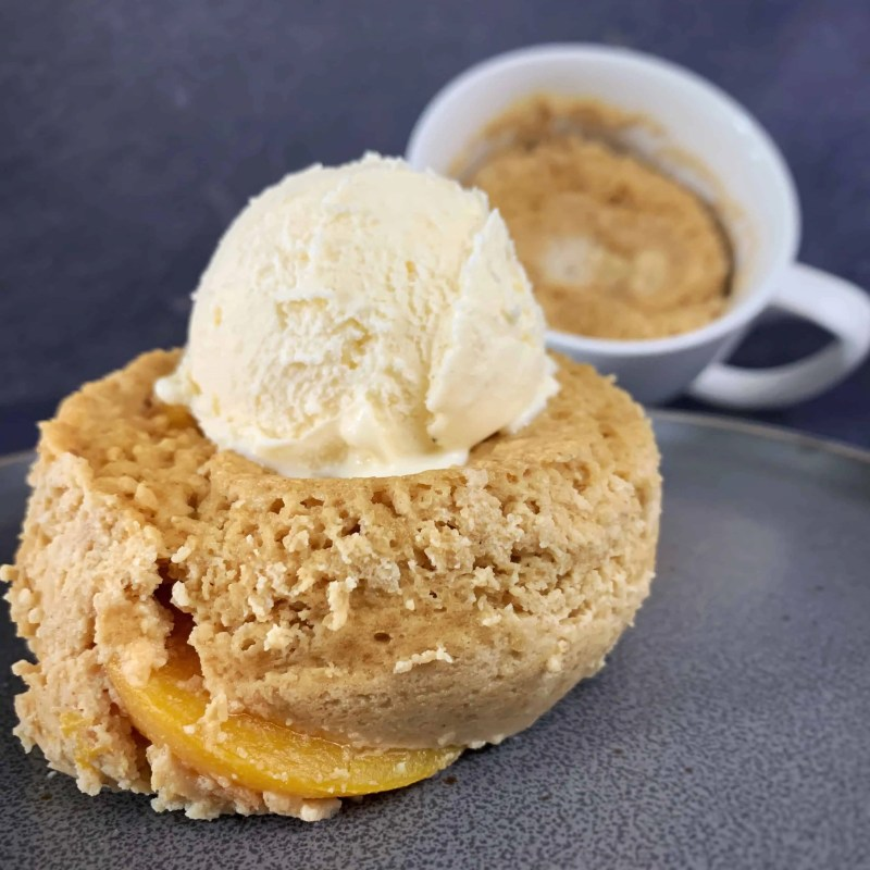 healthy peach cobbler mug cake on a plate with a second still in the mug behind it