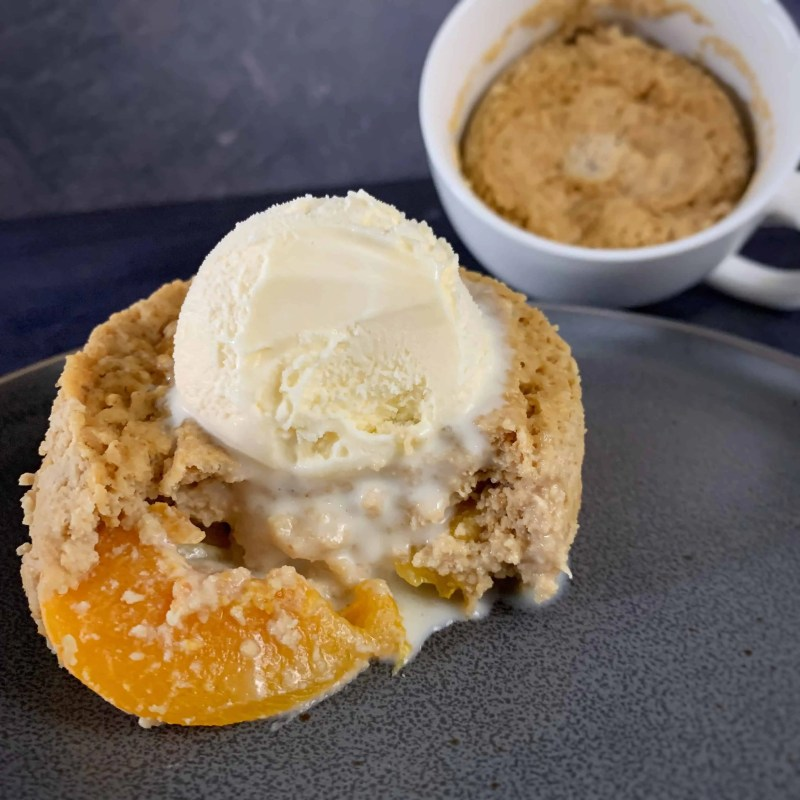 high protein peach cobbler in a mug