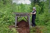 Eija Laitinen näyttää, kuinka kaivettu maa seulotaan, jotta pienimmätkin löydöt saadaan talteen.