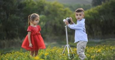 Dvě děti, chlapec v modré košili s fotoaparátem a dívka v červených šatech si spolu hrají na louce