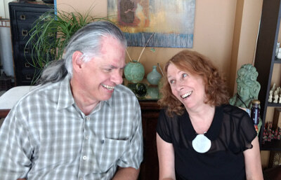 šedovlasý muž v šedé kostkované košili a žena v černé halence. Jsou v obývacím pokoji, na pozadí je obraz, oba se smějí.